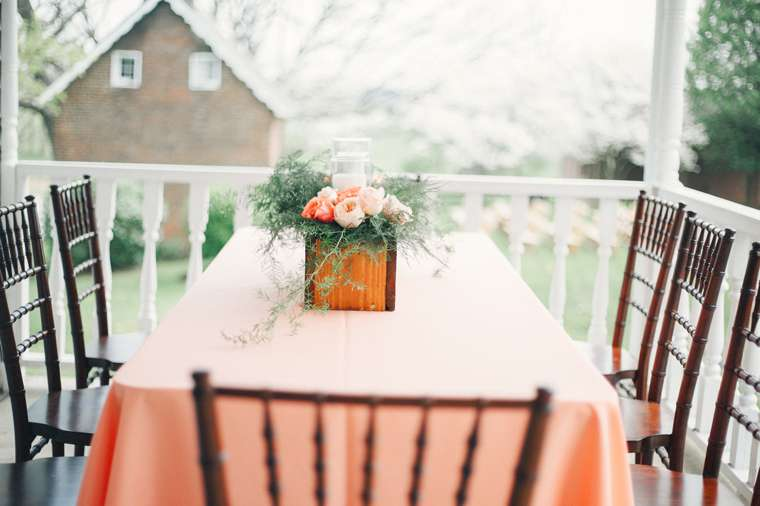 Peach and pink table setting with box flower arrangement at spring outdoor wedding reception