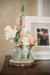 Spring bud vase flower arrangement on entry table at Warrenwood Manor wedding reception