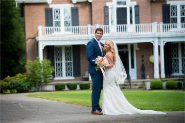 Bride and Groom in front of gothic style historic home