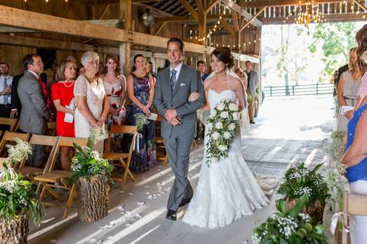 Bride and Father of the Bride enter traditional barn wedding ceremony