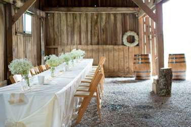 Banquet style wedding recpetion with ivory table linens, burlap runner and baby's breath flowers