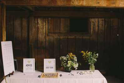 Entry table at barn wedding, yellow & white