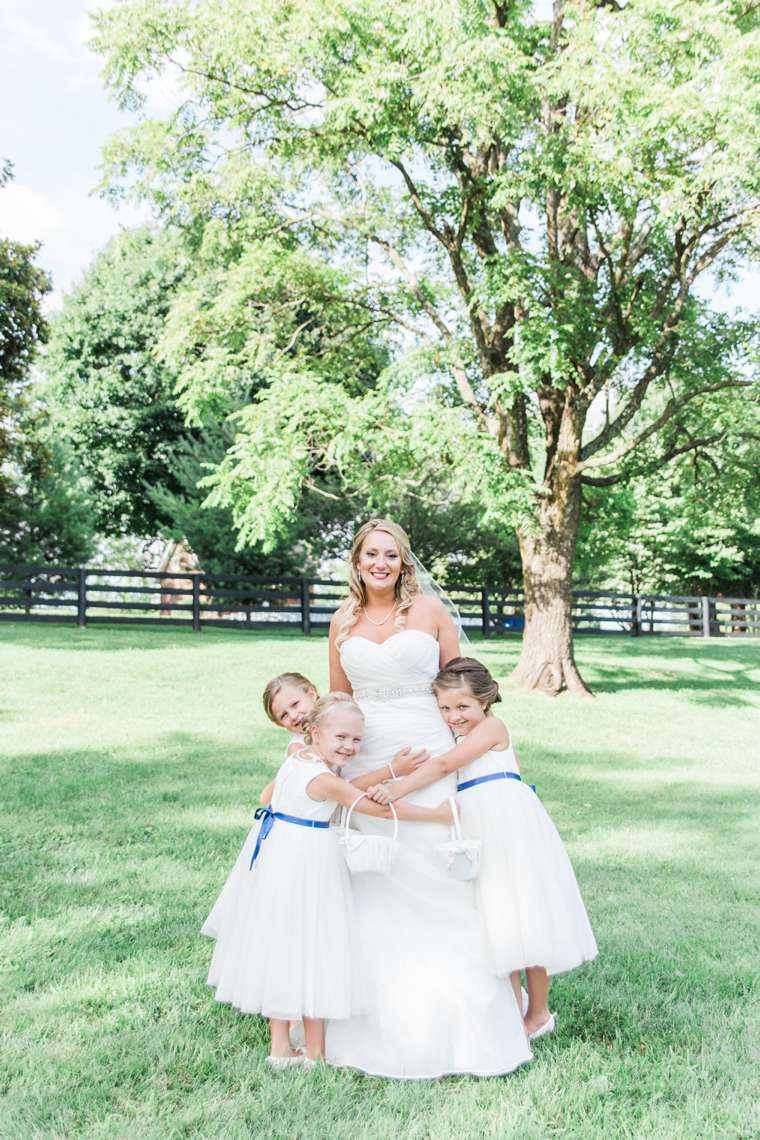 Flower girls in white dresses with navy belt