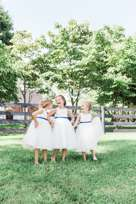Flower girls in white dresses with navy belt at Kentucky farm wedding