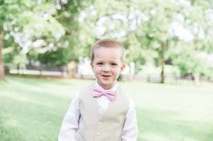 Dapper ring bearer in khaki vest, white shirt and pink bow tie