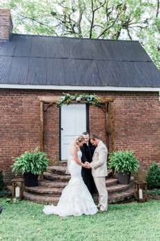 Backyard summer wedding ceremony with greenery-covered arch and ferns