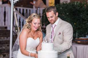Cake cutting during traditional outdoor wedding reception