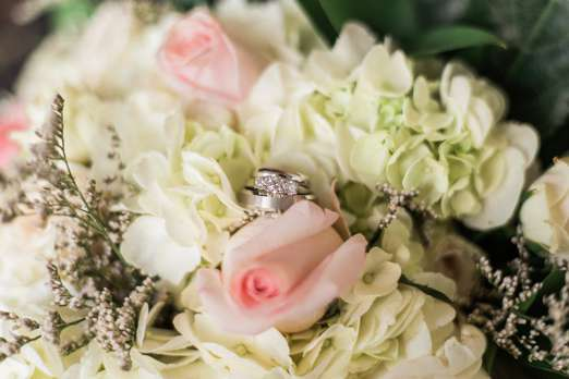 Ivory and pink flowers with wedding rings