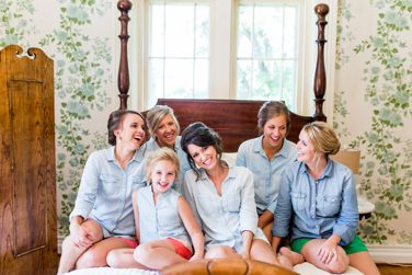 Bridal party getting ready in chambray shirts and bright shorts