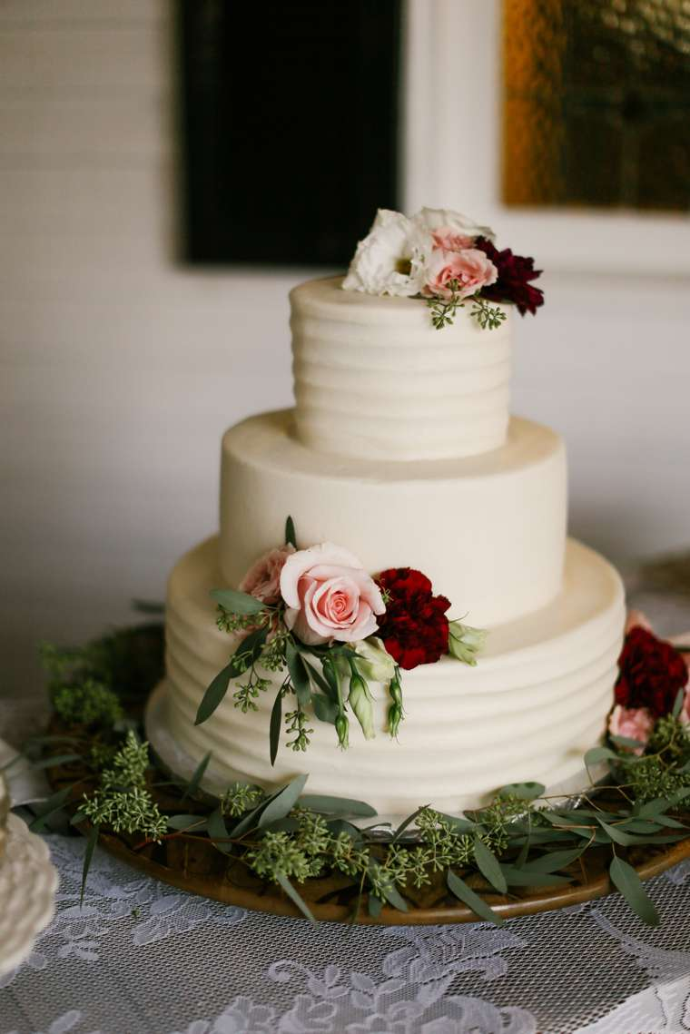 Simple textured ivory three-tier wedding cake with dusty pink and burgundy flowers with eucalyptus