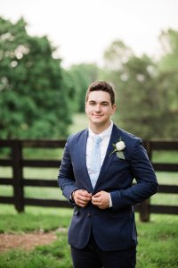 Groom in navy suit with light blue tie and white boutonniere