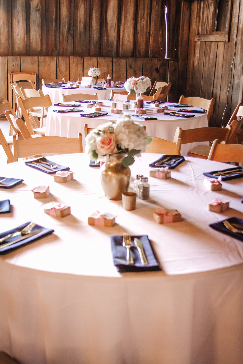 Pale pink and navy tables at country glam barn wedding