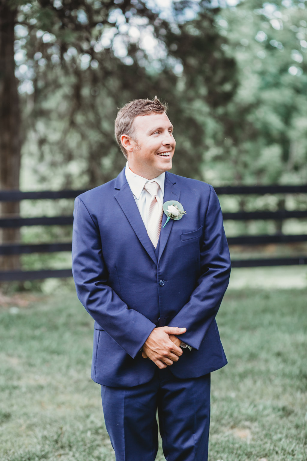 Groom in navy suite with pale pink tie for country glam wedding