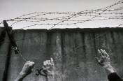 East and West German hands join in tearing down barbed wire from top of the wall on December 1, 1989.