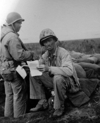 127-GW-329-112426: After returning from the front line, Sergeant William Purdum rests and reads mail received on Iwo Jima. He was a member of the Twenty-Eight Marines. Photographed by R. H. Stotz, 4 March 1945.