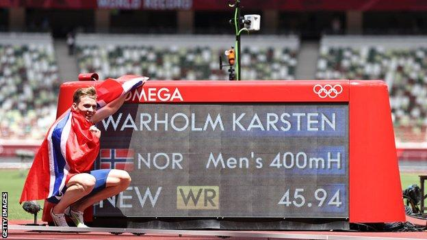 Karsten Warholm poses with the world record time