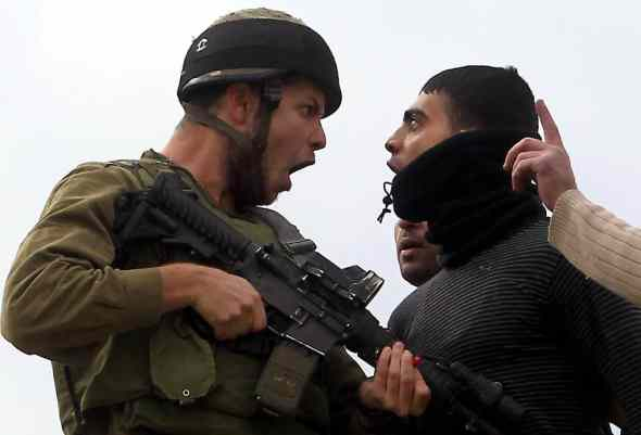 TOPSHOTS  A Palestinian resident of the northern West Bank village of Madama argues with an Israeli soldier after security forces came to intervene in clashes between Palestinian farmers and Israeli settlers from the Yitzhar settlement, on December 17, 2012, in the Israeli-occupied West Bank, near Nablus.   AFP PHOTO/JAAFAR ASHTIYEH