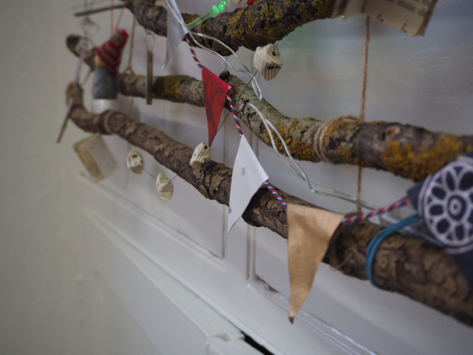 Christmas wrapping paper bunting hanging on branches of wood, part of the Warwick Events Advent Calendar blog