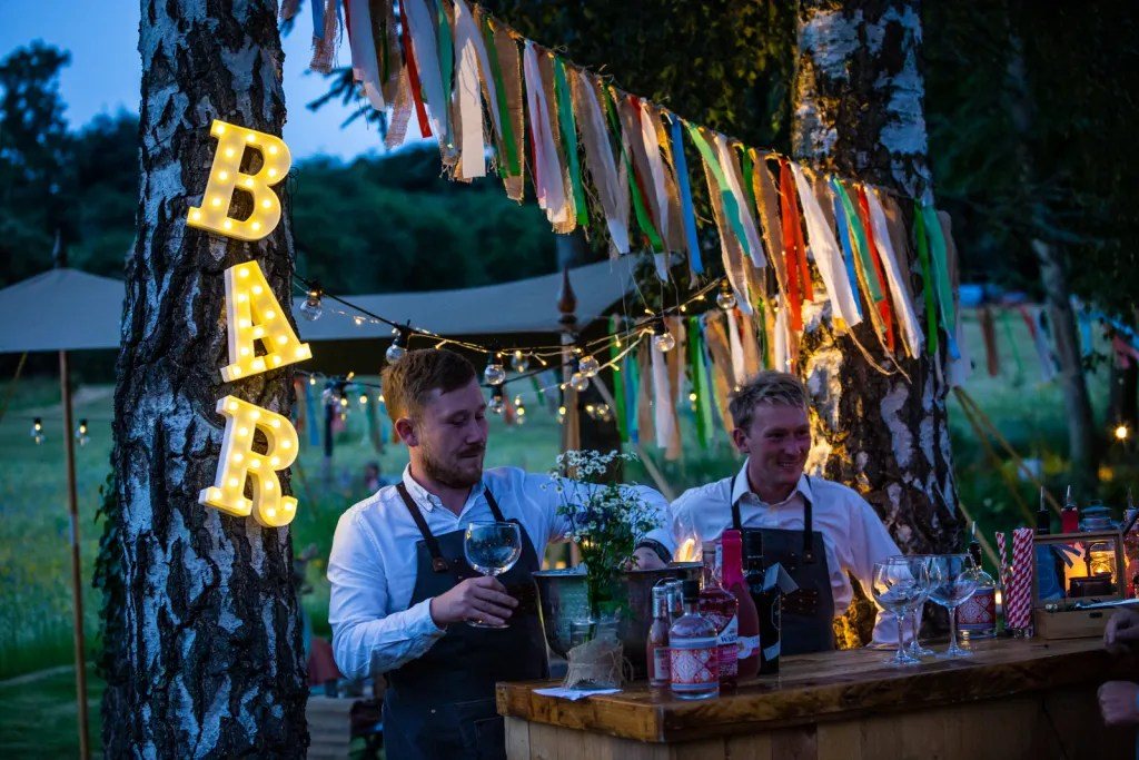 Night scene of popup cocktail bar decorated with ribbon bunting and lit up BAR sign hanging from tree for rustic-chic party