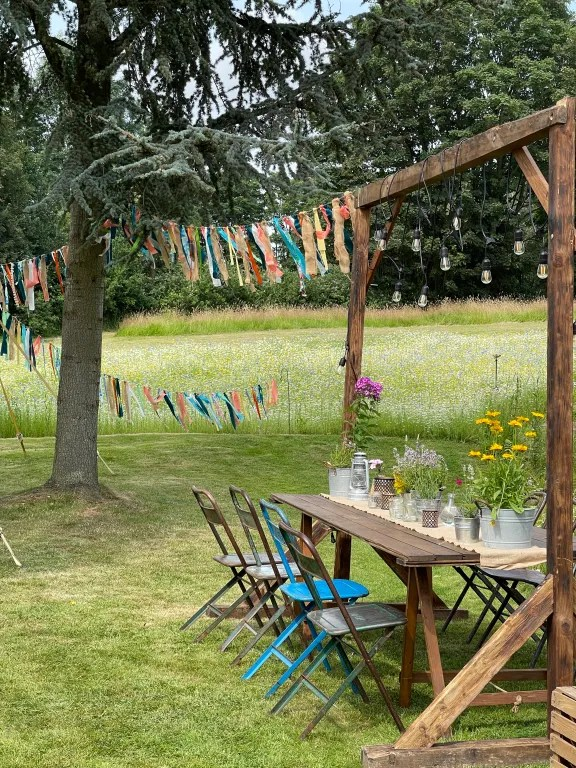 Trestle tables, fold out chairs, colourful ribbon bunting and festoon lights with wild meadow flowers in background