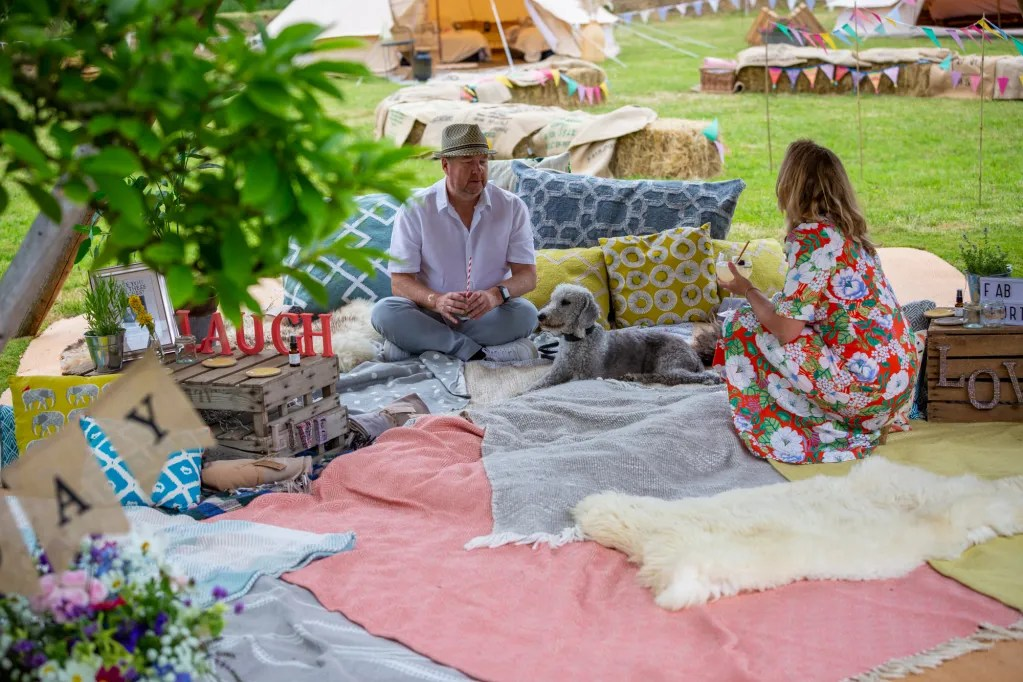 People chatting sat and crouched on blankets and cushions under chillout tipi at rustic-chic party
