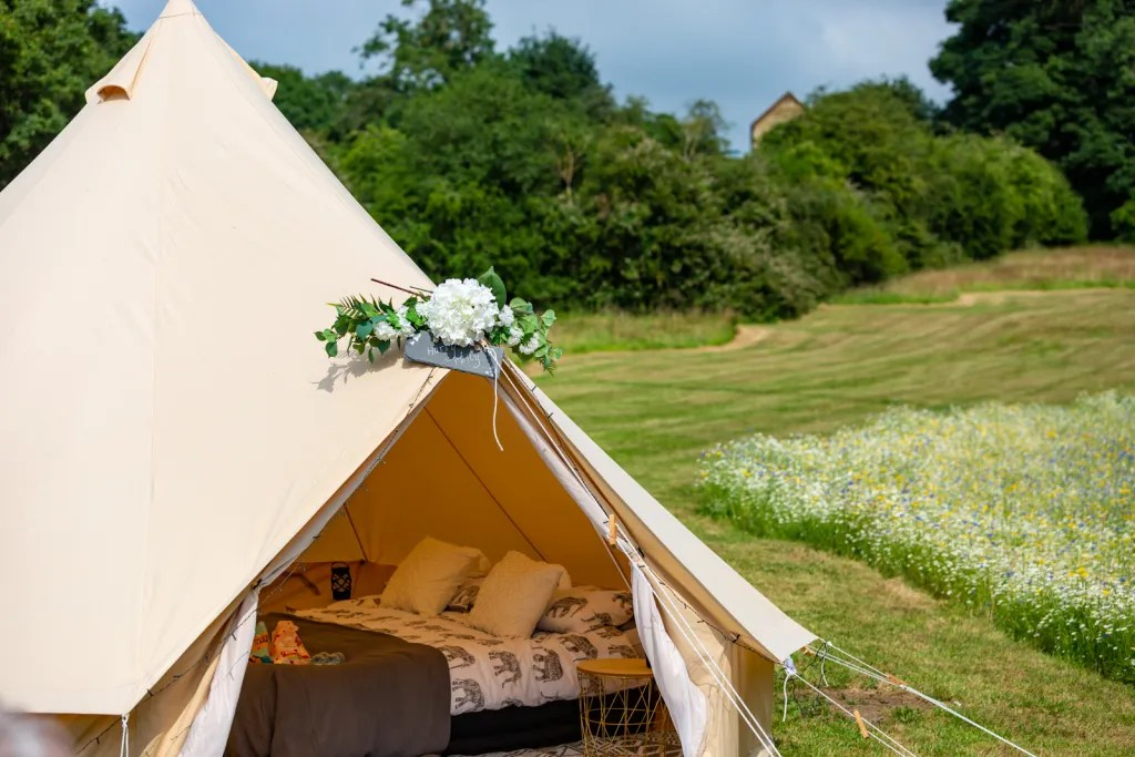 Glamping bell tent with double bed, meadow flowers in background