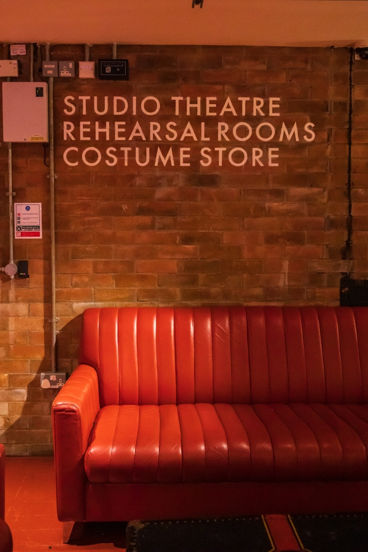 """Red leather sofa with sign above """"Studio theatre, rehearsal rooms, costume store"""""""