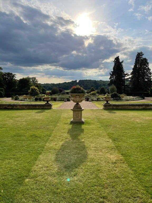 Urn of flowering plants in grounds of stately home gardens, the setting for VIP hospitality
