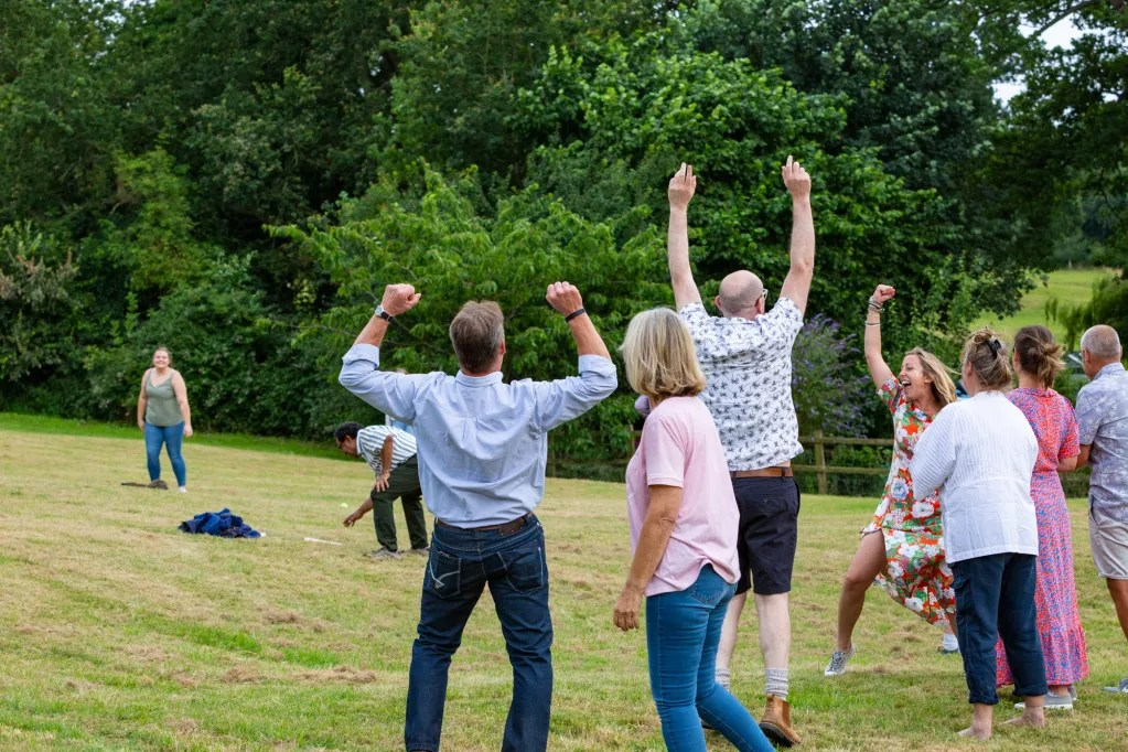 People cheering at rounders match