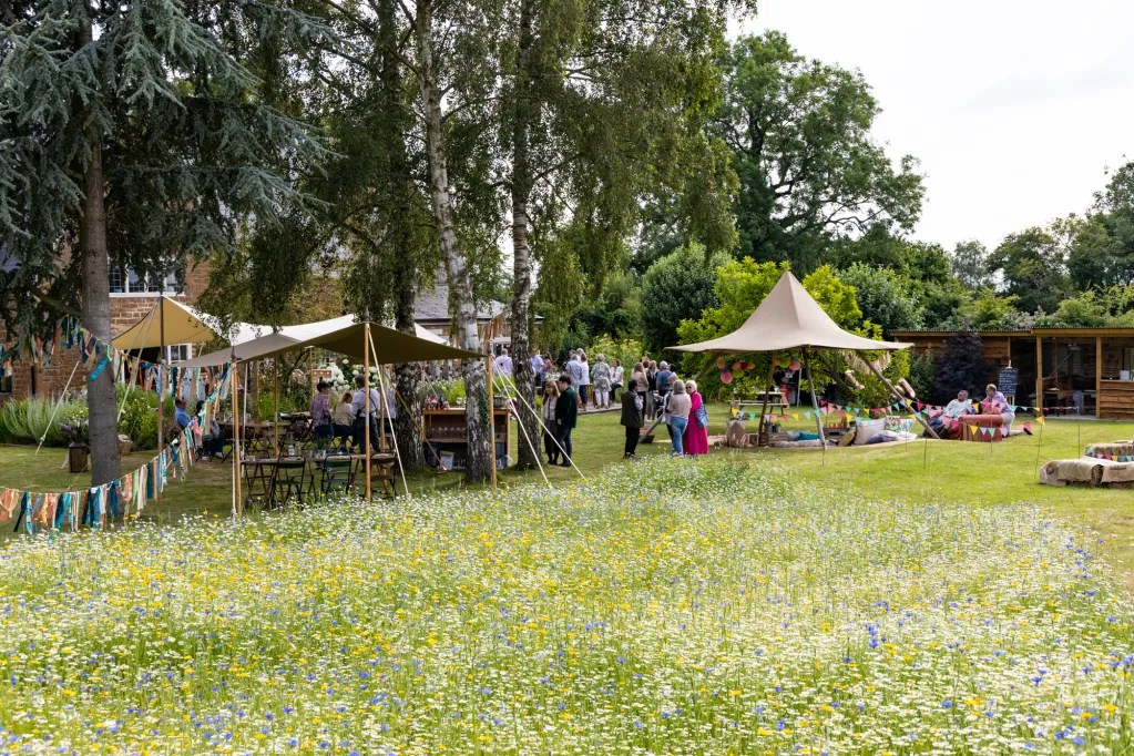 Tipis and canopies at rustic-chic party with meadow flowers in foreground