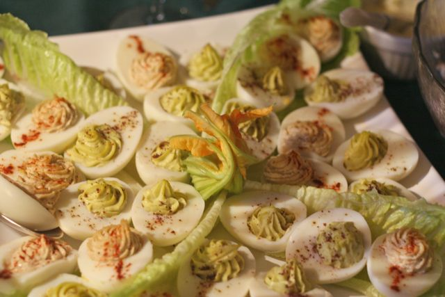 White plate with stuffed eggs with wasabi and avocado and lettuce leaves as a garnish