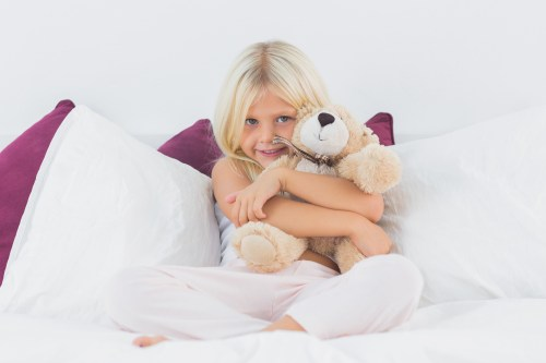 Little girl embracing her teddy bear on a bed