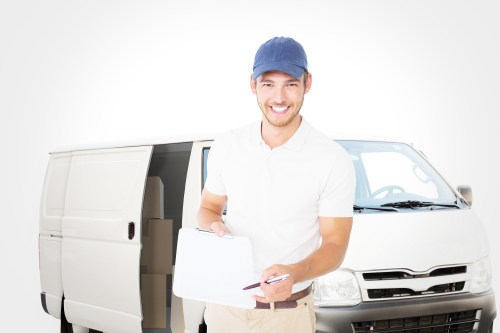 Happy delivery man holding clipboard against white delivery van