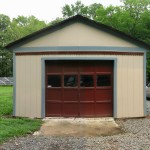 Front of garage shows dark red door, beige painted walls and blue trin with gravel driveway in front and between the garage and house