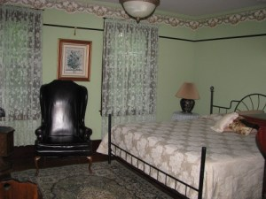 The king size bed, a large chair and one of the three windows can be seen in this view