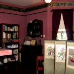 Maroon painted walls with paper trim and wood picture rail over large book cases plus curtains on windows and