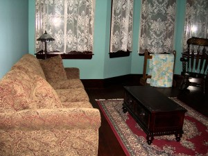 Victorian-look sofa with end table on throw rug and bay windows covered with lace curtains are shown