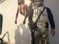 U.S. supplied Shia militiaman stands with his Sunni victim.