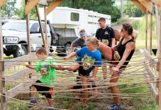 From left, Brevin, Abby and Kim Leggett maneuver through rope web. Cowboy 5K. Washington County Rodeo Saturday.