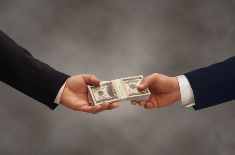 Two hands of businessmen passing a stack of dollars