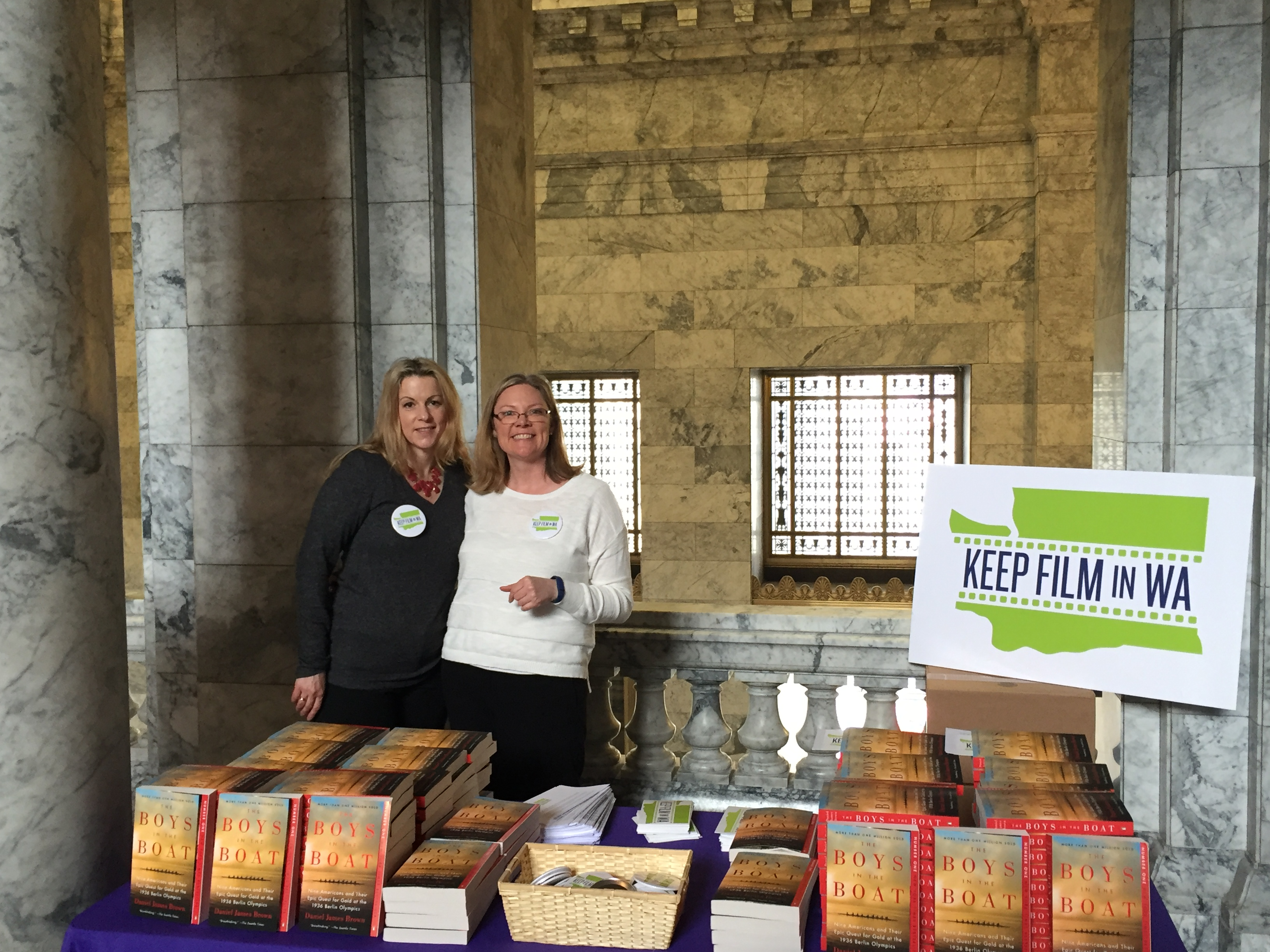 "Amy Lillard and Krys Karns from WF distribute ""The Boys in the Boat"" books to legislators at the Capitol on Monday."