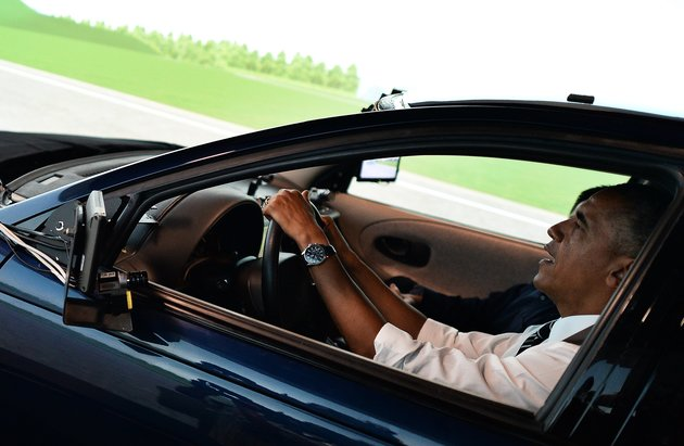 US President Barack Obama drives a simulator of a high-tech car as he tours the Turner-Fairbank Highway Research Center in McLean, Virginia, on July 15, 2014 before speaking on the economy. AFP PHOTO/Jewel Samad (Photo credit should read JEWEL SAMAD/AFP/Getty Images)