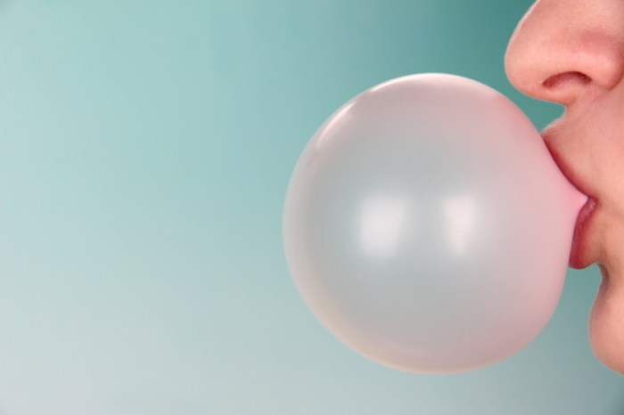 Person-doing-bubble-with-chewing-gum-on-bright-background