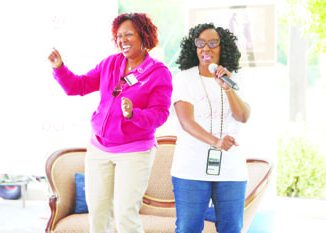 Dr. Regina Hampton, a general surgeon at Doctors Community Hospital, and Victorianne Russell Walton of It's in the Genes pumps up the crowd at a P.I.N.K.I.E. party for Breast Cancer Awareness Month in Lanham, Maryland, in October. (Courtesy of Doctors Community Hospital)