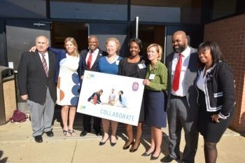 Prince George's County Executive Rushern Baker (3rd from left), Carol Thompson Cole (4th from left), president and CEO of Venture Philanthropy Partners, and Suitland High School Principal Nate Newman (2nd from right) stand with other partners in front of Suitland High School's Annabelle Ferguson Auditorium in Forestville, Md., on Nov. 4 to announce Venture's partnership with county schools to raise $15 million for a college-prep program. Photo by Roy Lewis