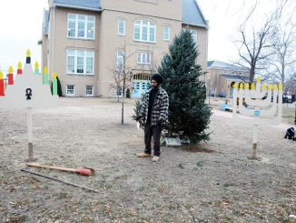 A worker makes preparations for Kwanzaa and Hanukkah celebrations with installations at the Congress Heights School in Southeast on Friday, Dec. 16.