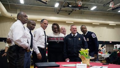 "From left: Prince George's County Sheriff Melvin High, Deputy Chief Raphael Grant, Fire Chief Marc Bashoor, PGF/EMS Batallion Chief C.H. Hunt, Assistant Fire Chief Alan Doubleday, and Capt. Kevin Hughes pose with local resident Anna Godfrey at the fifth annual ""District 7 Review"" and dessert reception at Hillcrest Heights Community Center on Dec. 18."