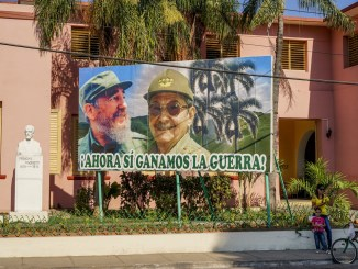Santiago de Cuba, Cuba - January 12, 2016: Typical scene of one of streets in the center of Santiago de cuba - Big poster of Raul and Fidel Castro. people walking around. Santiago is the 2nd largest city in Cuba /Photo: iStock