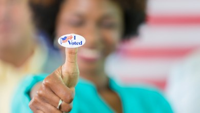"Smiling african american woman with an ""I voted"" sticker on her thumb. /Photo: iStock"