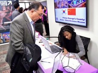 Prince George's County Economic Development Corporation Account Assistant LeSha Jean Francois checks in a business owner at an information session for an upcoming business mission trip to Korea and China. (Courtesy of PGCEDC)